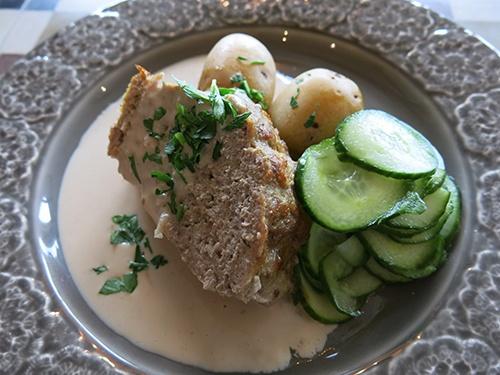 Köttfärslimpa med ramslök, gräddsås, kokt potatis och pressgurka.