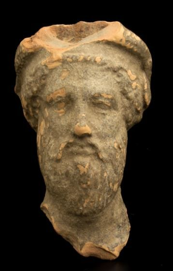 Greek terracotta head, Tarantine terracotta head of Dionysus, 4th century B.C. Greek head with luxuriant beard and drooping moustache, hair tied back in a headband and wreath decorated, 9.6 cm high. Private collection, from ACR auction