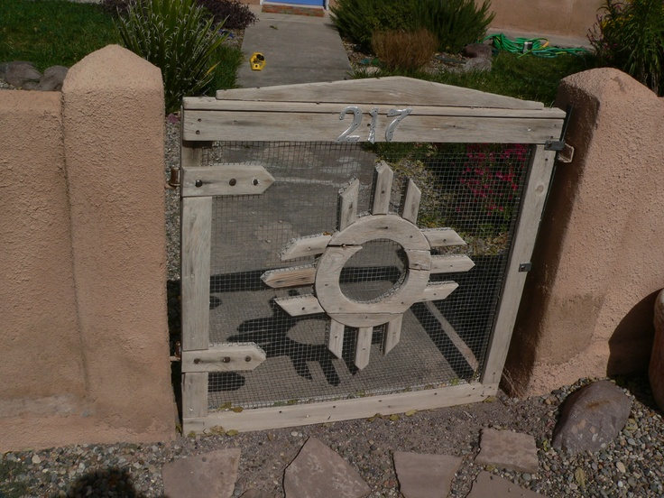 Rustic wire and wood gate in adobe wall, from Socorro New Mexico. It's wood and hardware cloth.