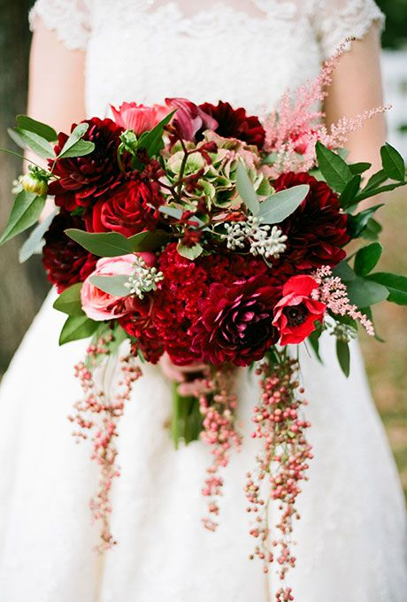 A Rustic Red Bouquet with Cascading Details. A red bouquet made of roses, anemones, and mixed greenery created by Cedarwood Weddings.