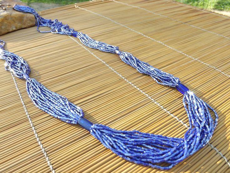 colar comprido de vidrilhos  e tubos de vidro azuis.
