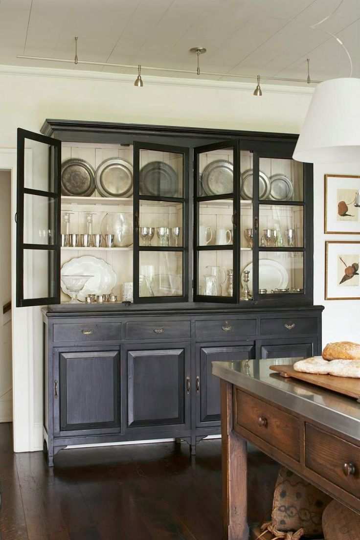 A traditional charcoal gray hutch displays beautiful dinnerware in this classic white kitchen. Track lighting illuminates the hutch's contents, making the display an eye-catching focal point.