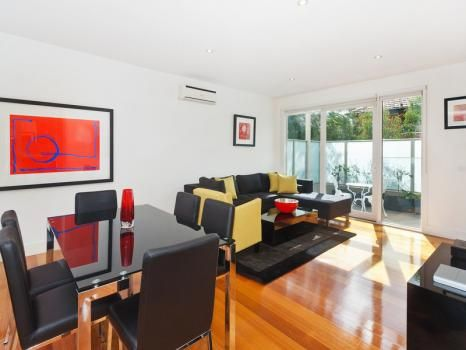 21/10 Tennyson Street, St Kilda, Melbourne. A superb location for St Kilda apartment living perfect for short stays, family or executive apartment rentals.  Comprising of 2 bedrooms, the main bedroom features a queen bed and deluxe marble en-suite while the second bedroom has 2 single beds. A second bathroom is also featured. The open plan kitchen is furnished with quality German appliances and marble bench tops.