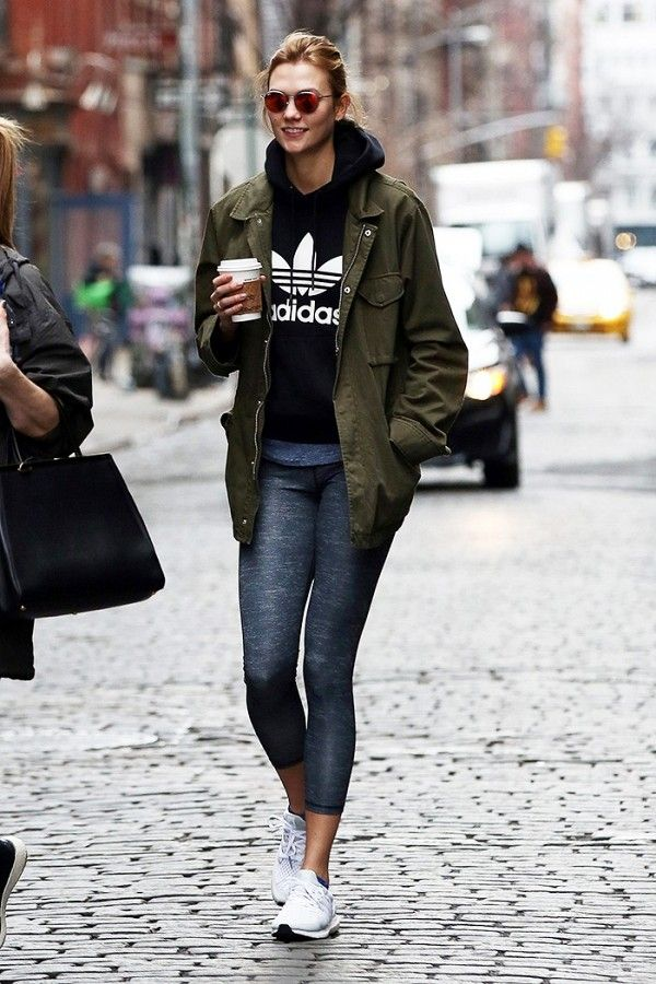 Karlie Kloss looks off-duty chic in an Adidas sweatshirt, army jacket, leggings, and sneakers.