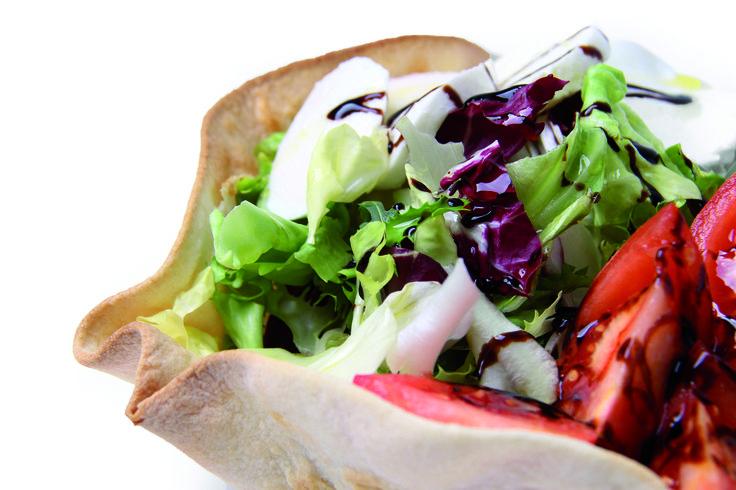Insalata in crosta di pane. Voglia di leggerezza? Provate a gustare un'insalata veloce, pronta in pochi minuti, contenuta in una base piadina dalla forma invitante, da condire a piacimento con prodotti freschi e genuini.