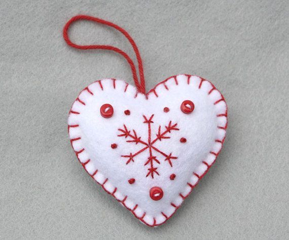 Red and white felt Christmas ornaments.  Set of 3 white felt hanging hearts, hand-embroidered with a red snowflake pattern, finished with three tiny buttons and a loop for hanging. Each of the three hearts has a different embroidered snowflake pattern.  Height 7cm/2.75 inches  White with red embroidery and buttons.  You can see the red snowflake ornaments in the last picture, and more felt heart ornaments here; https://www.etsy.com/ie/shop/PuffinPatchwork?ref=hdr_shop_menu§ion_id=19324374…