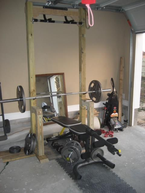 Garage workout station with pull up bar. Made with 4x4 treated lumber and wide as a standard door frame for the pull up bar. Use conduit clamps to secure the pull up.
