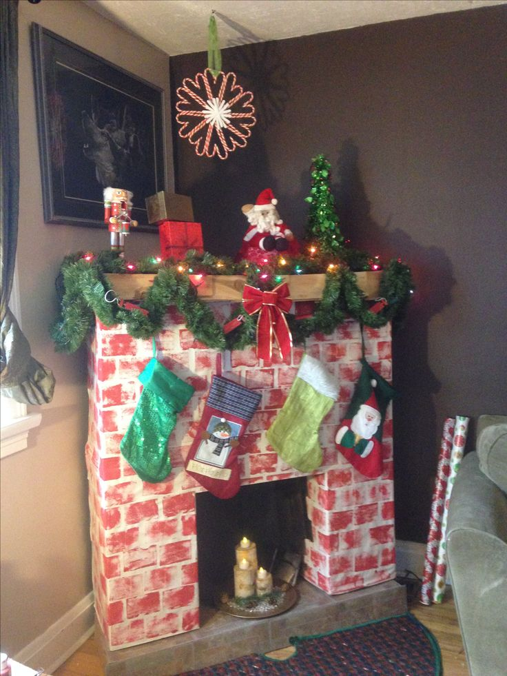 After sponging on some red paint for bricks, I decorated with garland lights, flameless candles, etc.. our stockings were to heavy for the fireplace, so they were placed on the couch!
