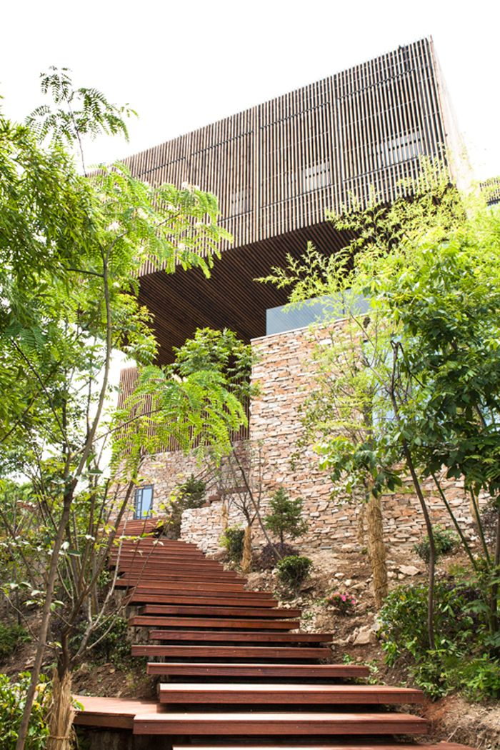 Overhang at Spa-Clubhouse, Garden Valley - Mei Jie Mountain Hotspring resort in Liyang, China. by AchterboschZantman architecten #walkway #slats #wood #overhang #bamboo #forest #shutters www.meijieresort.com
