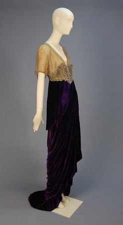 "TRAINED VELVET BELLE EPOCH GOWN with JEWELED BODICE 1913. Lush royal purple panne silk having short sleeve silk lace V-neck bodice asymmetrically draped in gold metallic mesh, high jeweled midriff band with center clear and magenta paste butterfly, hobble skirt layered over short train. Label ""Joseph 632 Fifth Avenue New York CYCLAMEN"""