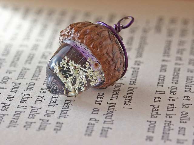 Stunning resin acorn with dried flowers inset. The top of the resin bit is backed with purple enamel and then glued into the cap.