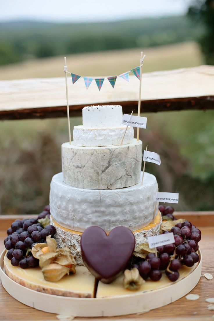 Cheese tower with mini bunting cake topper - Image by Dasha Caffrey - Rustic Wedding With Tartan Accents And Bride In Elegant Gown From Go Bridal With A Sassi Holford Veil And Rachel Simpson Shoes With Groom And Groomsmen In Kilts