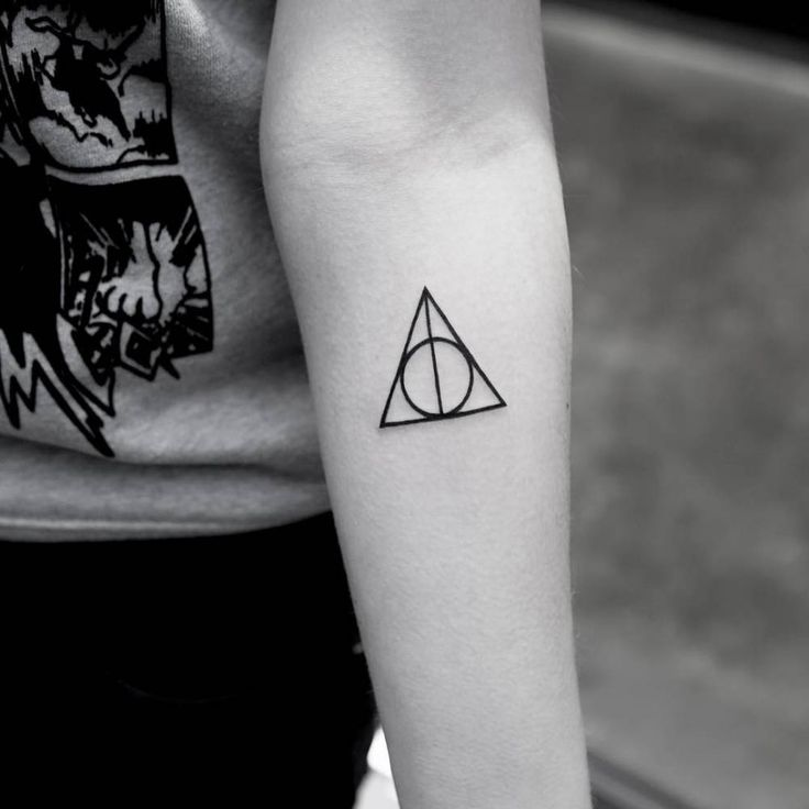 Deathly hallows symbol tattoo on the left inner forearm.