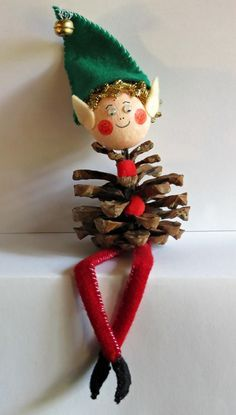 Make this cute Pine Cone Elf and sit him on your bookshelf or let him dangle his legs over the edge of an end table. #FaveCrafter