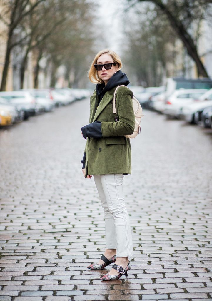 Sonia Lyson wearing Miu Miu shoes, Dior saddle bag, green oversized cord blazer Mango, Mango pants, hoodie Koenig Souvenir, Celine sunglasses on January 2, 2018 in Berlin, Germany.