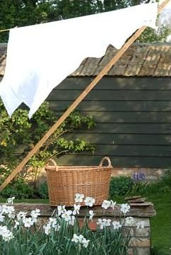 clothesline with a wooden prop to hold lovely linens high enough to catch the breeze and keep them from dragging the ground....nirvana.....love the wicker laundry basket too