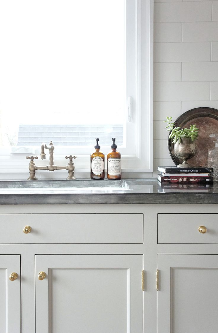 MAKE KING:  Putty colored kitchen cabinets with brass hardware.  Zinc counters.
