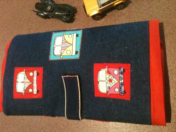 Car Mat all folded up and velcroed to close. Cars are inside for play and transporting. One of the other pins shows the inside with road made from felt and white lines appliqued on road.