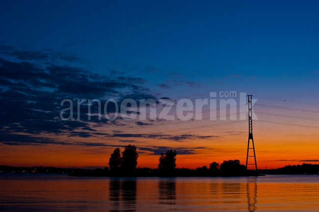 Sunset with silhouettes of trees and an electricity tower  © Arno Enzerink / www.stockphotography.nu All rights reserved.