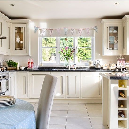 Country-style cream kitchen | Like the handles and glass front cabinets as well as the expansive window above the sink.