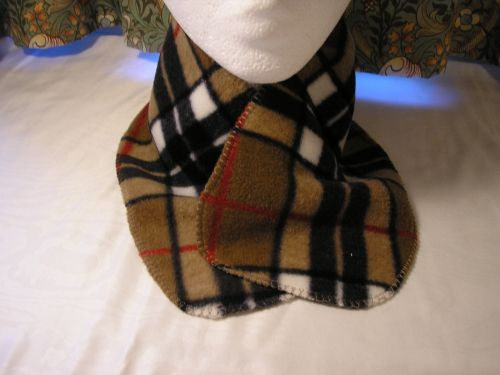 Shaped neck scarf in ever popular brown, black and white tartan. Soft fleece to tuck into your coat neckline. Warmth without weight.