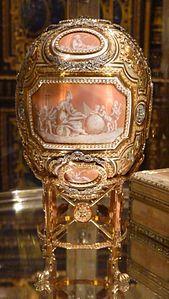 1914 Catherine the Great (Fabergé egg). L'uovo, senza il suo supporto, è alto 12,065 cm.[2] ed è fatto d'oro di quattro colori, grisaille rosa e smalto bianco opaco, diamanti taglio rosetta oppure tagliati come una lastra sottile, perline, è foderato di velluto.[3]  Vari pannelli dipinti da Vassily Ivanovich Zuiev (n. 1870) in smalto rosa camaieu, come cammei, sono incorniciati da file di perline e festoni di diamanti e oro cesellato