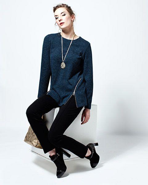 Tyylikäs sininen paita, jossa vetoketjuyksityiskohta helmassa. Mustat kapeat housut viimeistelevät asun.