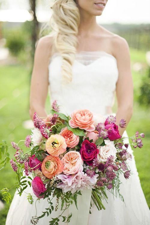 A large ranunculus wedding bouquet with dahlias, garden roses, astrantia, and jasmine vines | Brides.com