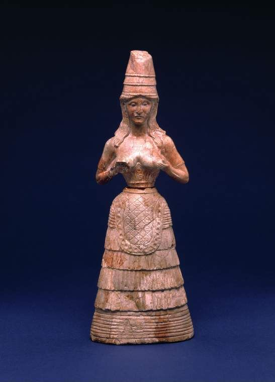 Minoan female statuette with hands raised to breasts    From Knossos on Crete.     This piece is fantastic for the study of Minoan fashion. She wears a tall conical hat, hair loose about her shoulders. She wears a dress with sleeves, which leaves her breasts bare. Under her breasts is a wide belt and an apron falls over her multi-layered skirt.