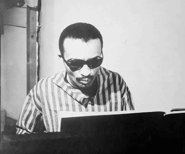 Photo of jazz legend Cecil Taylor seated behind the piano.