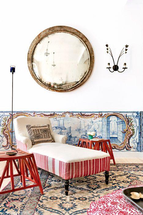 Los espejos redondos del salón provienen de una estación de tren de Polonia y fueron comprados en Bruno, un anticuario en la calle Clignancourt, en París. La gran alfombra en tonos azules es persa, adquirida en Christie's Londres. La chaise longue es francesa y está tapizada con gruesos y antiguos tejidos de ropa de cama y un tejido de la India con rayas rojas y blancas. El almohadón con estampado geométrico negro es de Mustapha Blaoui, en Marruecos. Las banquetas rojas a su lado proceden…