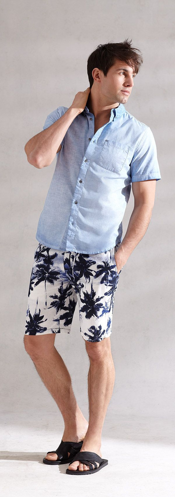 Comprar ropa de este look: https://lookastic.es/moda-hombre/looks/camisa-de-manga-corta-de-cambray-celeste-pantalones-cortos-estampados-blancos-y-azul-marino-sandalias-de-cuero-negras/11613   — Camisa de Manga Corta de Cambray Celeste  — Pantalones Cortos Estampados Blancos y Azul Marino  — Sandalias de Cuero Negras