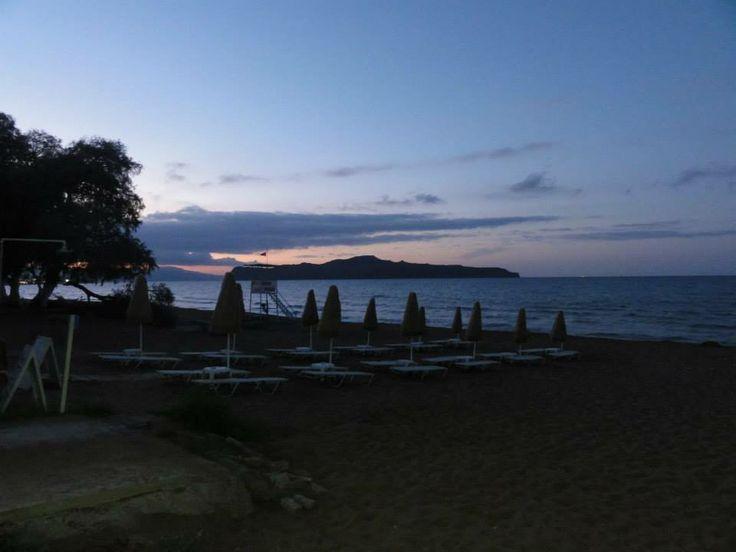 Strand bij zonsondergang Kato Stalos en het Krikri-eilandje