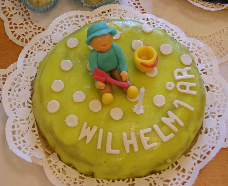 Grön prickig tårta med barn, hink och spade. Green polka dot cake with baby, bucket and spade.
