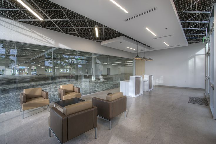 Alair Homes | Renovation | Warner | 12,000 sqft | 5 months | A sleek modern entry and reception area was created in this expansive commercial space, with a full glass wall separator. The bathrooms were also updated with a modern style to match.