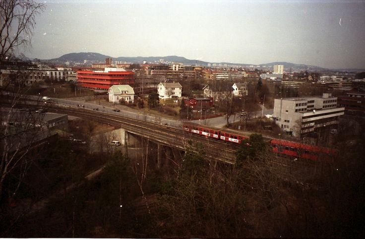 Oslo Bryn Til venstre bygningene til Joh. Petersen AS Lin og Bomullsvarefabrikk. Den røde bygningen til firmaet Brødrene Dahl markerer beliggenheten til Bryn gård som ble revet på tidlig 1980-tall. Nils Hansens vei går fra broen mot høyre. De to husene til høyre for den røde villaen midt på bildet er revet. Bygningen til høyre er Østensjøveien 56, Oslo Produksjon og Tjenester AS, skjermet bedrift etablert 1991, 123 plasser for yrkeshemmede. Bildet er tatt 20. april 1966