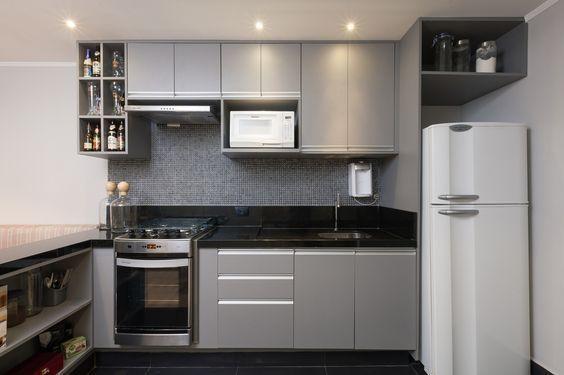 Ambientes integrados transformaram esse apartamento pequeno num espaço mais amplo e funcional. Cozinha com armários cinza e bancada preta, num decor masculino e moderno. Vem ver o projeto completo!