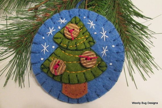 This forest green wool felt tree is hand cut in two pieces and blanket stiched onto a pretty winter sky blue wool felt ornament and decorated