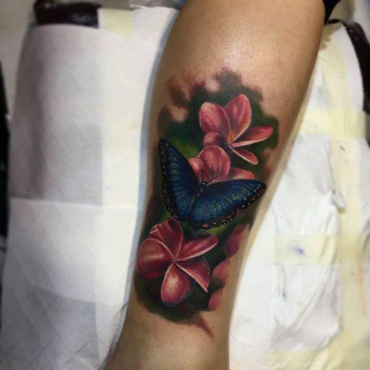 Tatuagem com borboleta azul e flor de pluméria.                                                                                                                                                                                 Mais