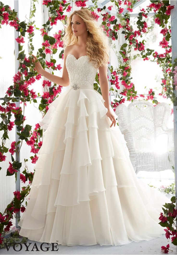 Wedding Dresses By Voyage featuring Venice Lace Appliqués on the Asymmetrically Tiered, Organza Gown Removable Beaded Satin Belt included, but also sold separately as Style 11237. Colors available:White, Ivory, Ivory/Champagne.