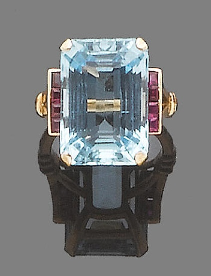 An aquamarine and ruby dress ring  Set to the centre with a cut-cornered step-cut aquamarine, between square-cut ruby shoulders,