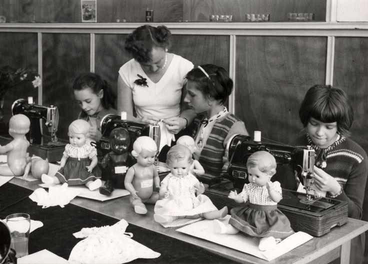 Een naaicursus op Singer naaimachines, om meisjes poppenkleertjes te leren maken. Nederland 1956.