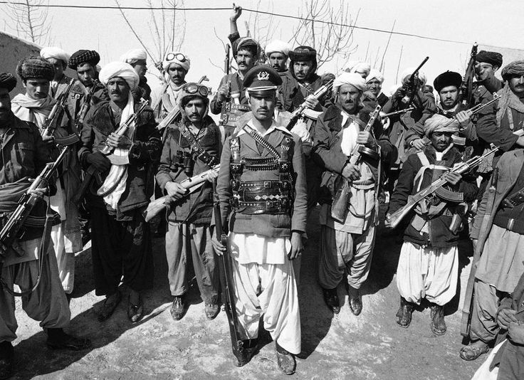 A mujahideen, a captain in the Afghan army before deserting, poses with a group of rebels. Afghanistan - 1980.