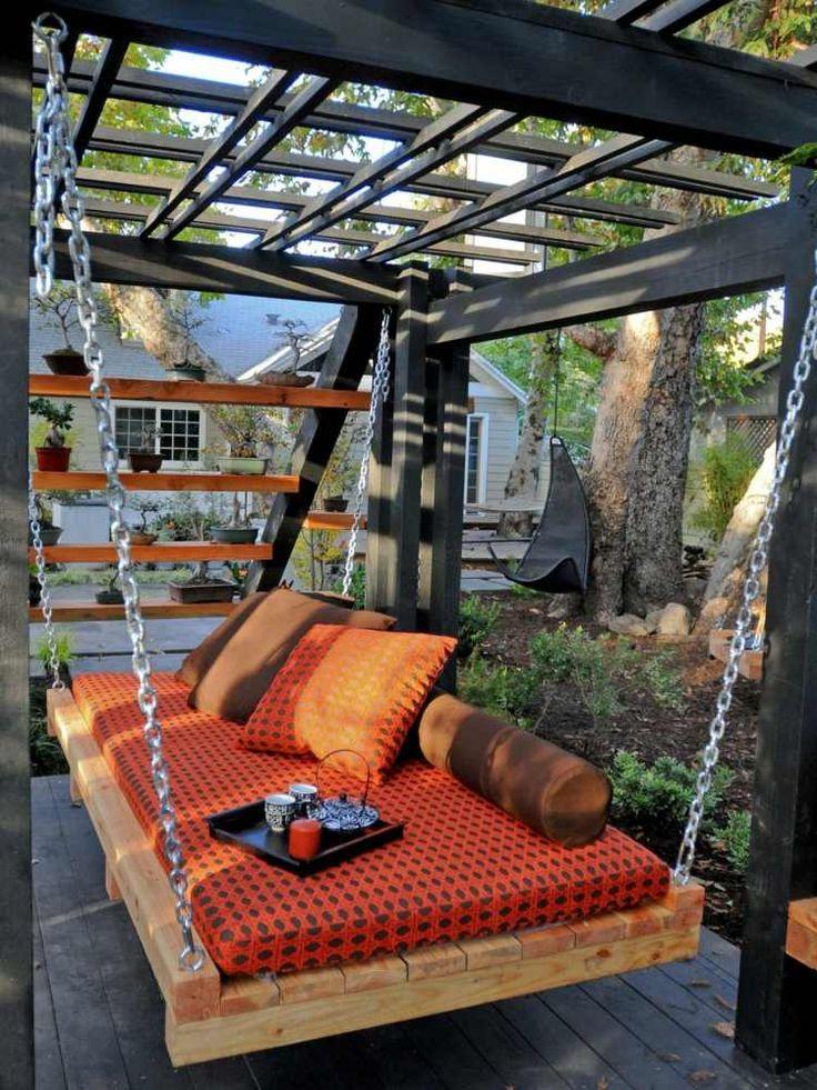 lit suspendu à la pergola en bois noir dans le jardin