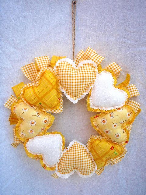 This wreath has a padded ring tied with raggy material strips coloured dark yellow and yellow gingham.. It is fronted with 8 hand sewn padded hearts, 2 white,2yellow gingham, 2dark yellow, 2yellow daisy patterned.  It has a brown string ready for hanging.  Size Approx 12ins across.