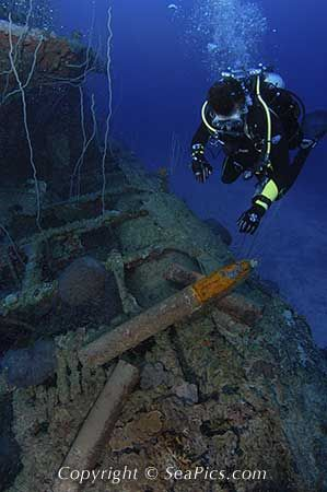 Scuba diver looks at live 5 inch shells on submarine wreck USS Apogon, Bikini Atoll, Marshall Islands, Micronesia, Pacific