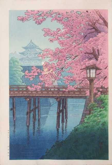 Trees laden with pink blossoms near a wooden bridge leading to a house