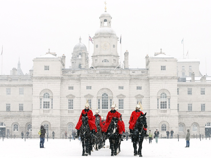 Horse Guards Parade, London  A snowstorm mutes all but the distinctive scarlet coats worn by members of the Household Cavalry Mounted Regiment, here crossing the Horse Guards Parade in central London. Famous for its mounted soldiers, Horse Guards comprises an ensemble of buildings and the Parade, an open space used for ceremonial events such as the Queen's birthday.