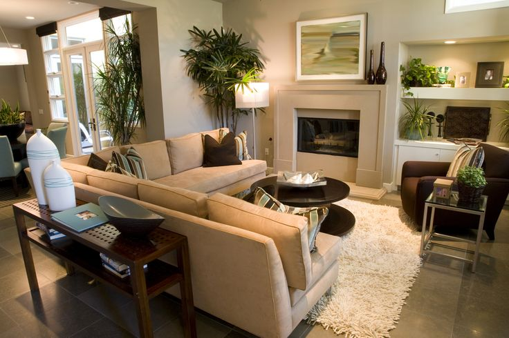 Great attention to detail in this very small living room space with L-shaped sofa, round coffee table and one large brown armchair all on an off-white shag rug.