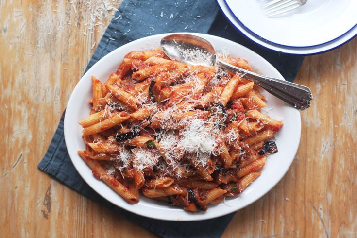 Pasta alla Norma (Eggplant and Tomato Pasta) 1 large eggplant (or 2 finger eggplants) Salt, to taste Olive oil for frying 2 garlic cloves, peeled and squashed One 14-ounce (400 grams) can of chopped tomatoes 11 ounces (320 grams) rigatoni, penne, or maccheroncini pasta 3 ounces (80 grams) grated ricotta salata 8 to 10 basil leaves, torn